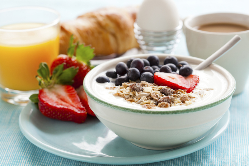 Bowl of muesli with yoghurt, strawberries and blueberries, boiled egg, orange juice, croissant and coffee for healthy breakfast
