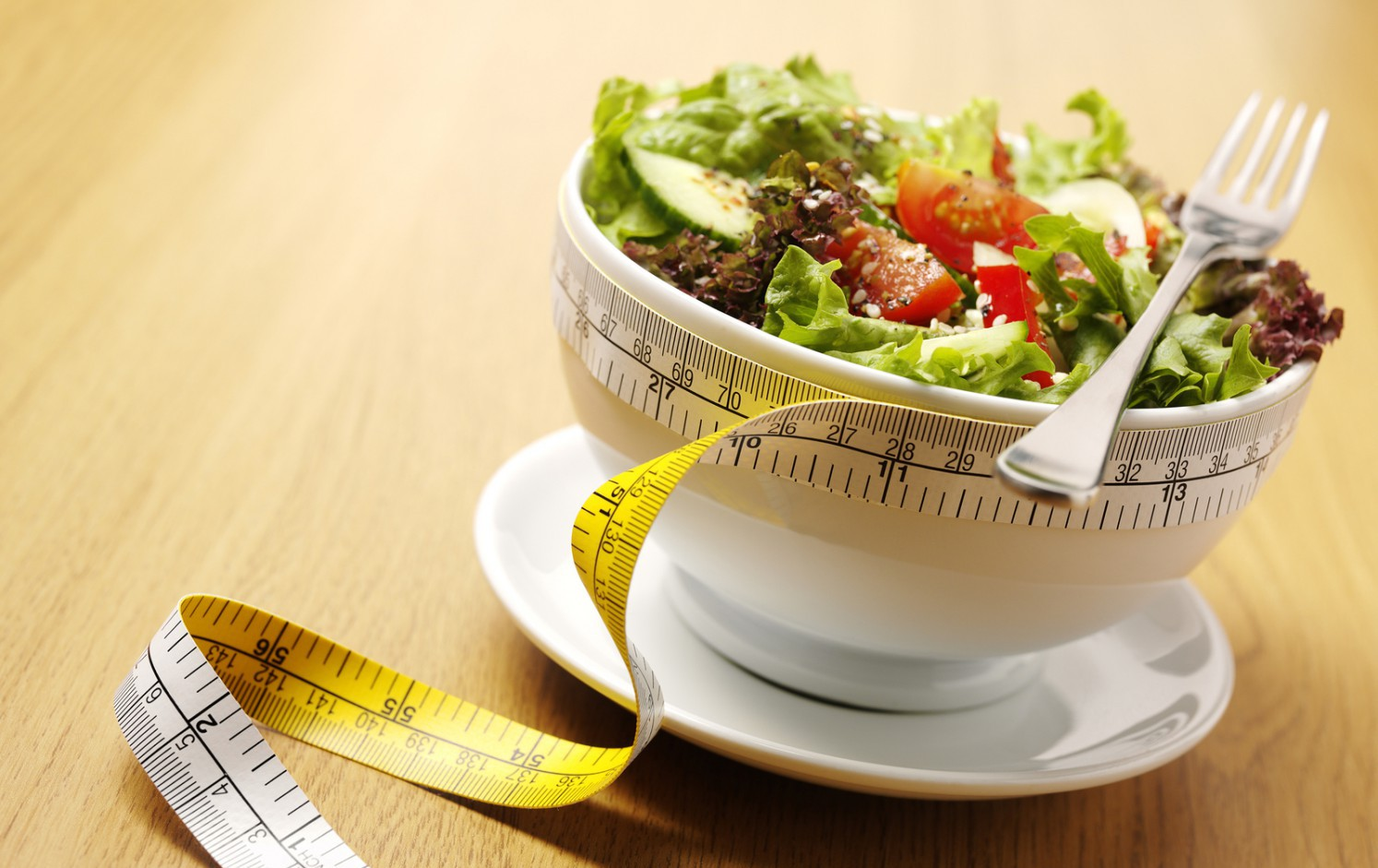 A bowl of mixed salad with a tape measure for healthy eating on a wooden background. ** Note: Shallow depth of field