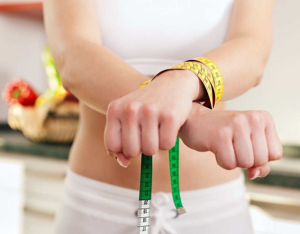 11529824 - woman handcuffed by a tape measure - symbol for eating disorder